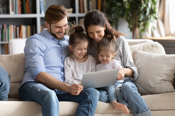 Happy young Caucasian family with small daughters relax on couch at home watching funny video on...