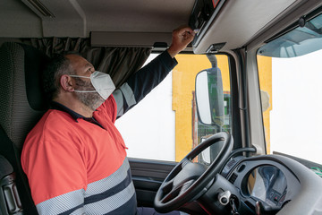Truck driver with mask inserting the card into the tachograph to start the activity.