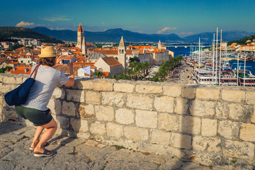 Tourist woman photographer is taking travel pictures with phone, Croatia