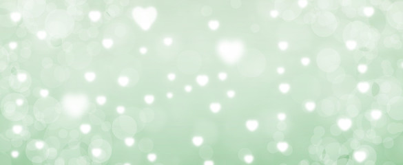 Glowing green bokeh background. Spring concept. Blurred bokeh circles and hearth shapes.  Website banner. Celebration.  Christmas. Wall mural