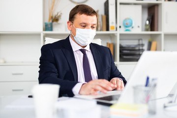 Man in protective face mask working at office