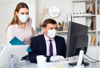 Manager in protective medical mask gives task to assistant