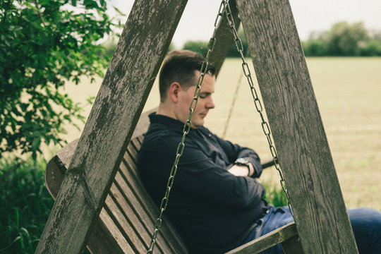businessman sits in wooden swing and relaxes