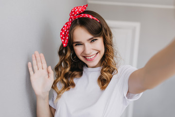 Wall Mural - Enthusiastic white girl with wavy shiny hair taking picture of herself at home. Indoor photo of happy female model with red ribbon making selfie.