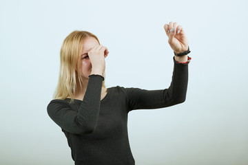 Young Blonde Woman In Black Sweater With Stylish Watch On White Background, Focused Girl Looking Through Her Hands Imitates A Telescope. Researcher, Scientist. Concept Of Smart And Purposeful People Wall mural