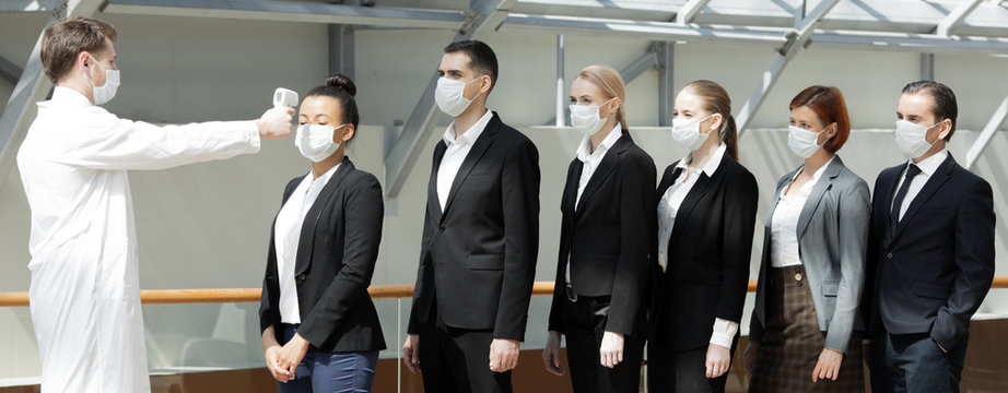 Doctor check body temperature of business team