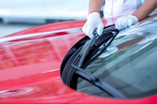The mechanic is changing the wipers in the parking lot. Change the wiper tires to prepare for the windshield cleaning while raining during the rainy season.