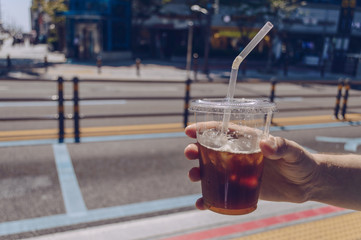 mans hand holding iced coffee cup
