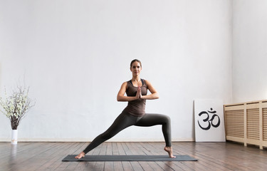 Young and fit woman practicing yoga indoor in the class. Stretching exercise in the day light....