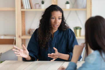 Close up confident african american businesswoman explaining new responsibilities to female applicant. Attractive young diverse woman hr manager talking and introduction company to job seeker.