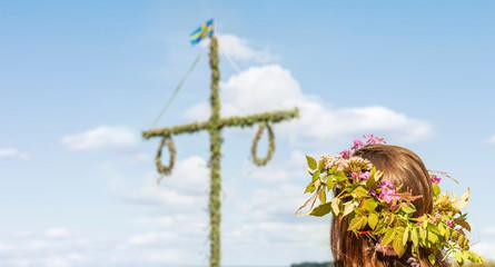 Mit Blumenkranz am Mittsommerbaum in Schweden