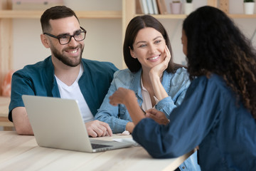 Real estate agent consulting happy young couple about buying house rent purchase mortgage in office...