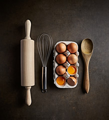 Baking utensils and raw eggs on rustic background. Home baking and cooking. Flat lay