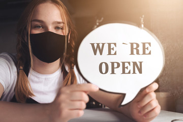 Coronavirus covid 19.Coffee shop woman owner with face mask, open after lockdown quarantine.End quarantine. Announcement we are open nv doors,  resumption shops, cafes,coffee houses, small businesses