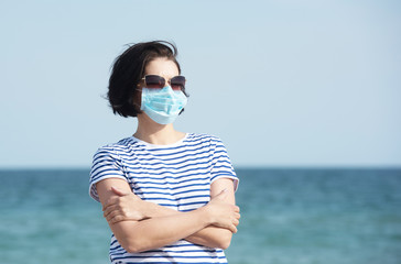 Young woman in a mask standing on empty coast, protective equipment during coronavirus covid19. Social distance concept.
