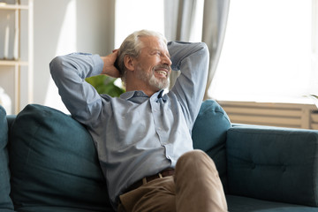 Relaxed happy grey haired mature old man enjoying free lazy weekend time on sofa. Tranquil calm peaceful smiling senior middle aged grandfather resting on couch alone, dreaming planning future.