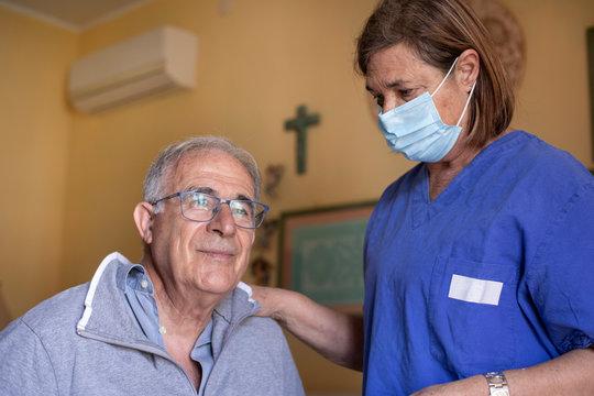 Infermiera con la mascherina facciale assiste anziano a domicilio seduto nel letto di casa sua