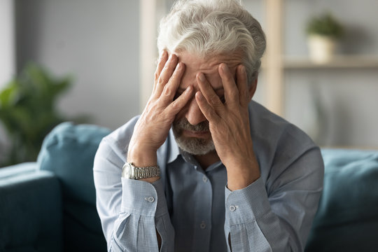 Frustrated unhealthy senior mature man touching head, having painful feelings sitting alone at home. Unhappy middle aged retired grandfather suffering from high blood pressure disease indoors.