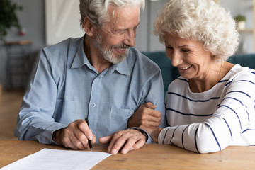 Happy senior older married couple discussing investing saving before signing paper agreement....
