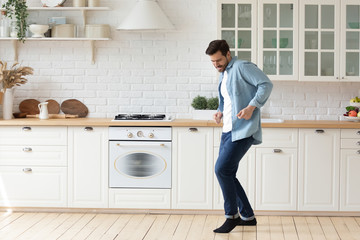 Happy millennial man enjoy leisure weekend dancing alone in bright modern design white kitchen,...