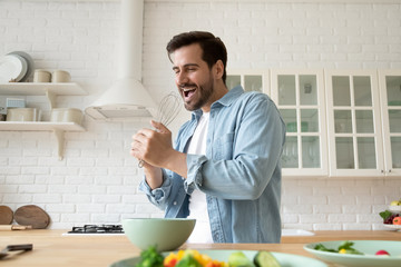 Happy young Caucasian man preparing food in modern design kitchen have fun singing and dancing,...