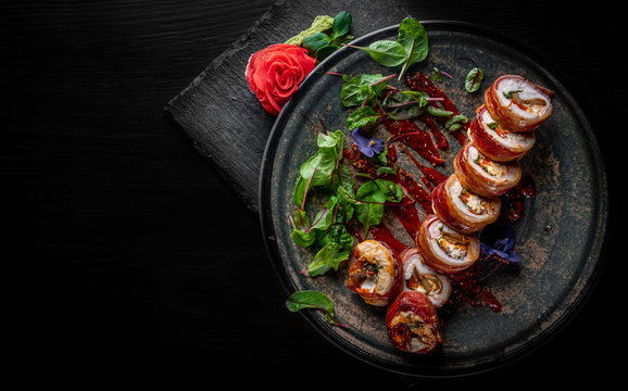 sushi rolls with bacon and chicken in plate on black wooden table background