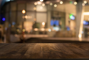 Close-up Of Table Against Illuminated Defocused Lights In Building - fototapety na wymiar
