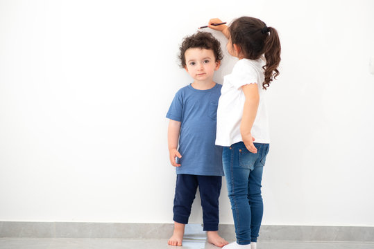 Cute girl measuring height of a funny child with curly hair. Sister measures the growth of her brother at a blank white wall.
