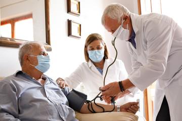 Anziano con mascherina viene visitato da un medico a casa che gli prende la pressione sanguigna...