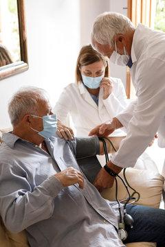 Anziano con mascherina viene visitato da un medico a casa che gli prende la pressione sanguigna insieme ad un altra dottoressa che assiste
