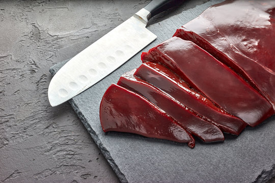 Fresh raw beef livers on a black stone cutting board  on dark background.