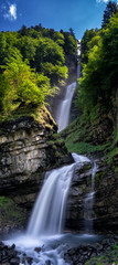 Wall Mural - vertical panorama of the idyllic Diesbach creek waterfall in the Swiss Alps near Braunwald and Glarus in the spring