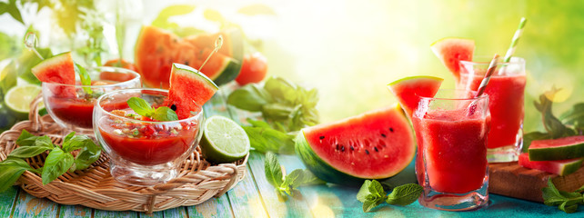 Summer refreshing watermelon drinks in glasses and cold soup gazpacho with basil on wooden table. Concept of healthy summer eating.