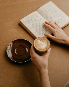 Book and coffee on a table with a woman's hands