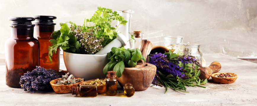 .Fresh herbs in mortar bowl from the garden and the different oils for massage and aromatherapy.