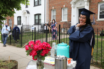 George Washington University graduate Perez beams as she receives a cake and flowers during a surprise graduation party by neighbors in Washington