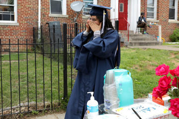 George Washington University graduate Perez wipes away tears as she receives a cake and flowers during a surprise graduation party by neighbors in Washington