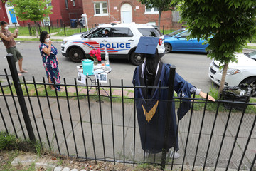 Police officers drive by to offer congratulations as neighbors keep a social distance and host a surprise graduation party for Perez during to the coronavirus disease (COVID-19) outbreak in Washington