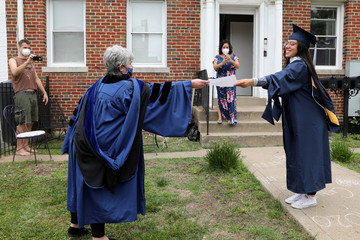 George Washington University graduate Perez receives a paper copy of her diploma from her neighbor at a surprise graduation party in Washington
