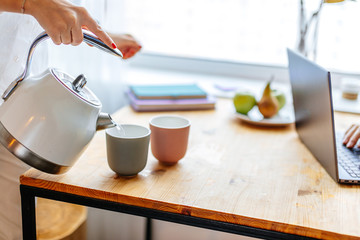 close-up photo of unrecognizable woman preparing coffee or tea. female pouring hot water from teapot into a cup. laptop on the table. morning