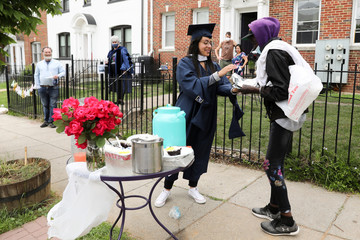 George Washington University graduate Perez shares her cake with a neighbor passing by during a surprise graduation party by neighbors in Washington