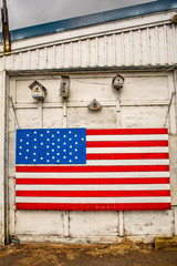 A large United States flag on the side of a garage with bird houses above it.