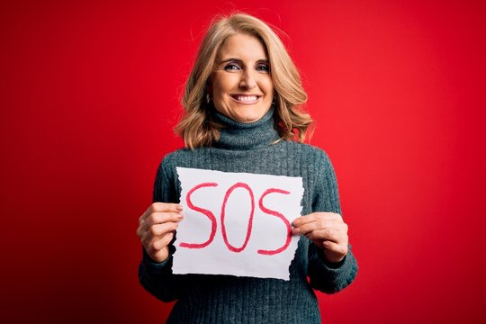 Middle age beautiful blonde woman holding paper with sos message over red bakground with a happy face standing and smiling with a confident smile showing teeth