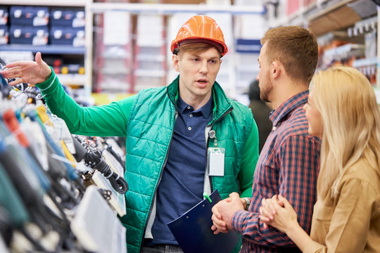affable caucasian male warehouse worker consult and help to customers, show the best variant of product in stock, married couple ask questions, interested in commodity