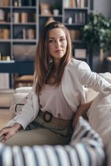 Woman sitting on sofa and looking at camera.