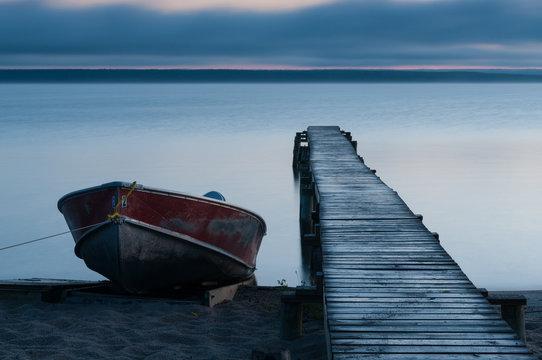 Aluminum fishing boat beside a dock on a calm peaceful lake before sunrise.