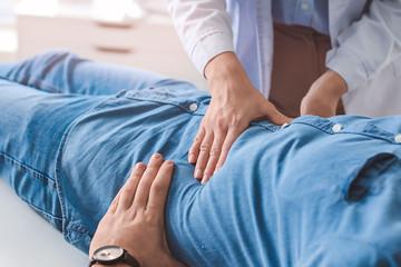 Gastroenterologist examining man in clinic