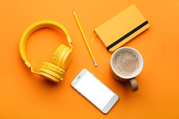 Modern mobile phone with headphones, notebook, cup of coffee and pencil on color background