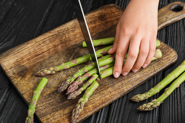 Woman cutting fresh asparagus at table