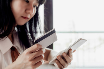 Asian woman holding a credit card and using smartphone for online shopping and payment concept